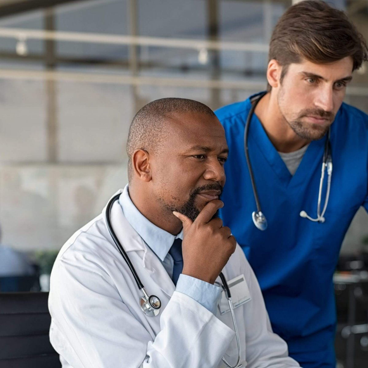 Mature african doctor and nurse analyze medical report on computer in office. Two healthcare workers in consultation using computer at hospital. Doctor discussing medical report with colleague at clinic.