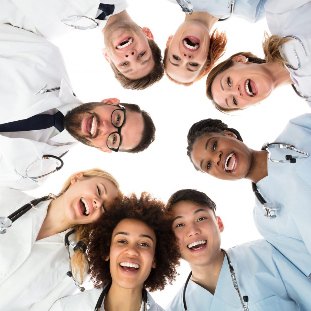 Low Angle View Of Smiling Medical Team Standing Against White Background
